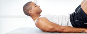 Man on yoga mat doing ab exercise